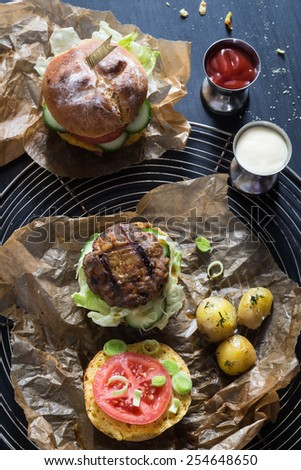 Homemade Juicy Pork Burger, a Veggie One with a Flag Topper and Buttered Baby Potatoes with Dill - stock photo