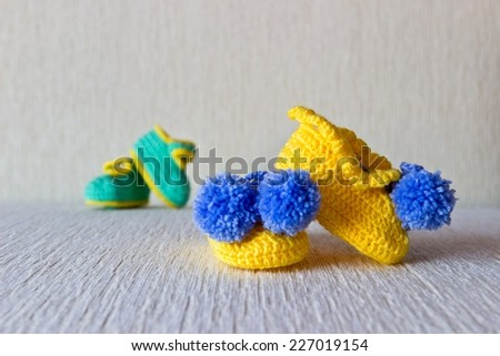 Homemade knitted small baby wool booties. Two couple. Selective focus - stock photo