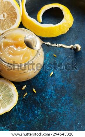 Homemade lemon curd in glass jar, with fresh lemons - stock photo
