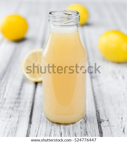 Homemade Lemon Juice on an wooden table (selective focus) as detailed close-up shot
