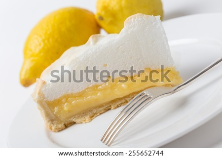 Homemade lemon meringue pie, a classic of European dessert cuisine, with lemons and a fork, shot at an angle - stock photo