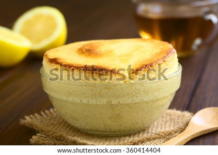 Homemade lemon souffle in glass bowl, with cup of tea and lemon halves in the back, photographed on dark wood with natural light (Selective Focus, Focus on the front of the souffle)