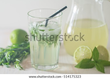 homemade lemonade from lime and tarragon on white wooden background