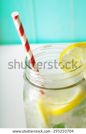 Homemade lemonade in a mason jar with big red striped straw  - stock photo
