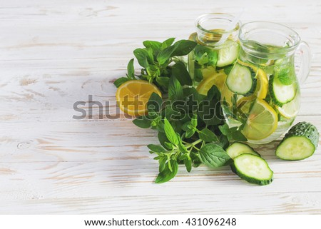 Homemade lemonade with fresh lemon, cucumbers and mint on white wooden background. Fresh water, refreshment drink - stock photo