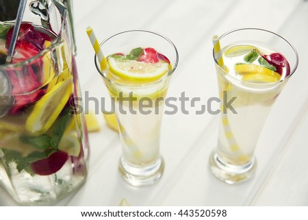 Homemade lemonade with lemon, strawberry and mint leaves in the summer day.