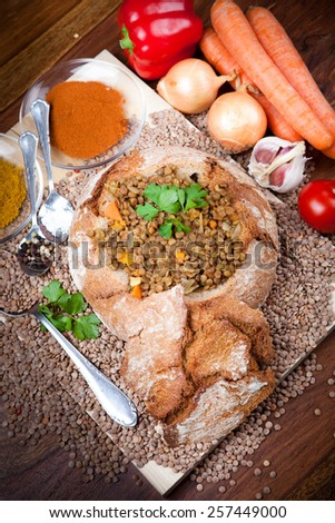 homemade lentil soup in loaf of bread served on wooden plate, with indian curry spice, vegetables and raw brown lentils around,   - stock photo
