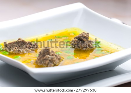 homemade liver dumplings in chicken soup with carrots and peas - stock photo
