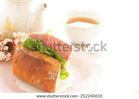 Homemade luncheon meat and lettuce sandwich with English tea on background