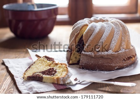 Homemade marble cake on table with one slice missing