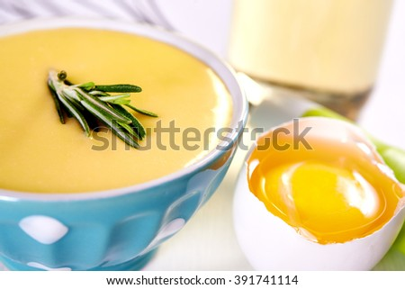 homemade mayonnaise in blue bawl and egg over white background