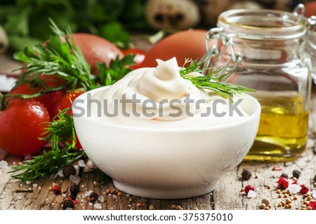 Homemade mayonnaise sauce in a white bowl, jar with olive oil, eggs, salt, spices, mustard, herbs, cherry tomatoes on old wooden background, selective focus - stock photo