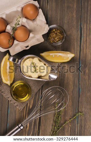 Homemade mayonnaise sauce with ingredients on brown wooden table. Top view. Space for text