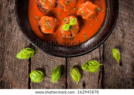 Homemade meat balls and tomato sauce in the old pan from above  - stock photo