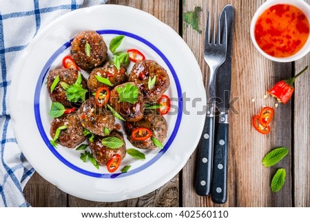 homemade meatballs with mint, green onions and chili sauce on wooden table - stock photo