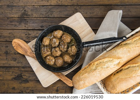 Homemade meatballs with onion sauce in a saucepan on the table - stock photo