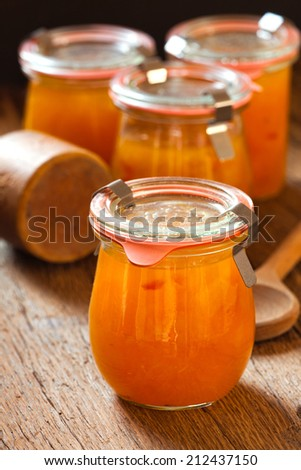 Homemade melon jam in a preserving jar on rustic wooden background in country style  - stock photo