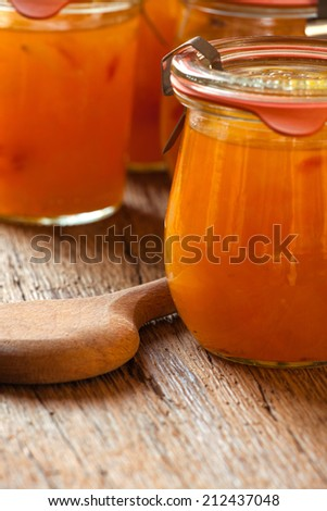 Homemade melon jam in a preserving jar on rustic wooden background with copy space - stock photo