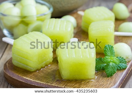 Homemade melon popsicles on a wooden background, closeup