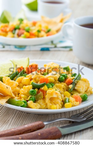 Homemade mexican salad scrambled egg served with baked corn tortilla chips and wedge of lime , healthy breakfast - stock photo
