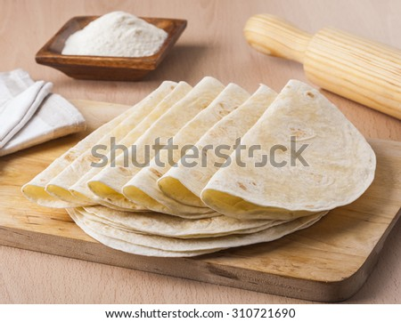 Homemade Mexican tortillas with flour and a rolling pin - stock photo