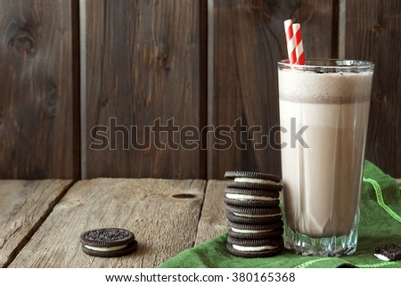 Homemade milkshake (chocolate smoothie) with cookies on rustic wooden table with copy space - stock photo