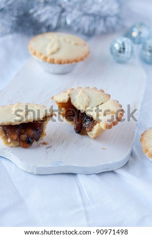 Homemade minced pies on a chopping board - stock photo