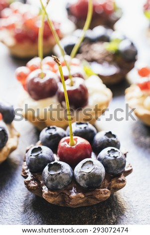 Homemade mini tarts stuffed with pudding and berry fruits,selective focus  - stock photo