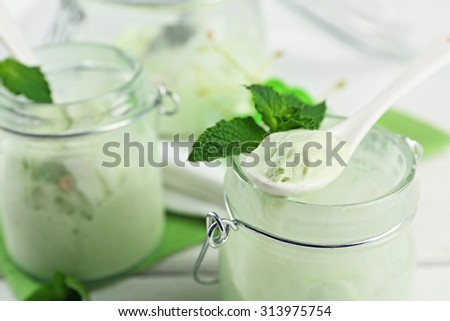 Homemade mint ice-cream in glass jars on light wooden background