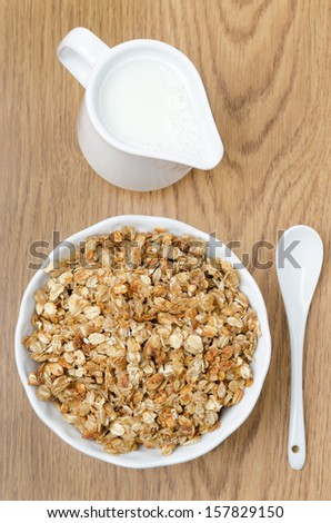 homemade muesli and a jug of milk for breakfast top view vertical - stock photo