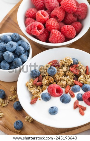 homemade muesli with fresh berries, nuts and yogurt for breakfast, top view, close-up, vertical - stock photo