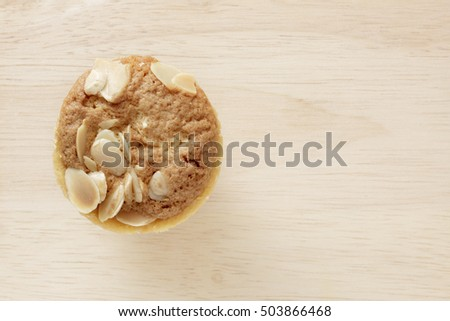 Homemade muffin on brown wooden background.