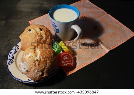 Homemade muffins and cup of milk on wooden background