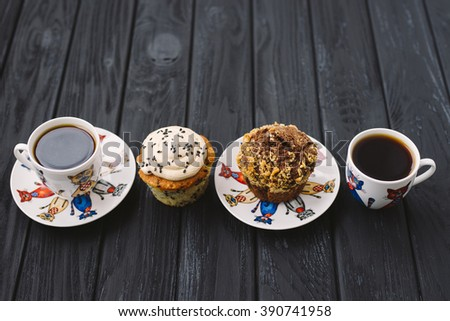 homemade muffins and two cups of coffee on black wooden background - stock photo