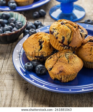 Homemade muffins with blueberries on a wooden background in a blue bowl. selective Focus