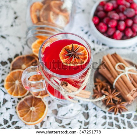 Homemade mulled wine with orange slices, cranberries, cinnamon and anise on wooden table. The rustic style. Soft focus - stock photo