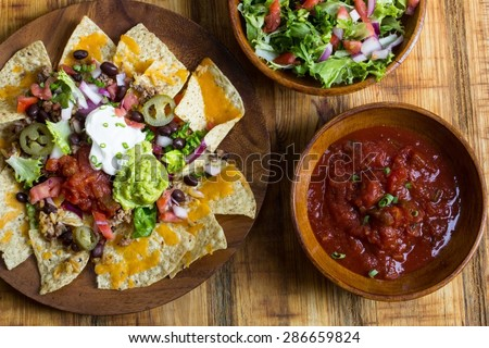 Homemade Nachos with tomato salsa and spring salad, overhead view - stock photo