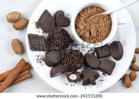 Homemade natural chocolate candies with ingredients on white plate. - stock photo