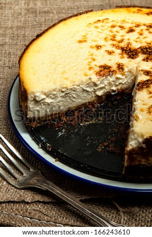 Homemade New York cheesecake with a slice missing - stock photo