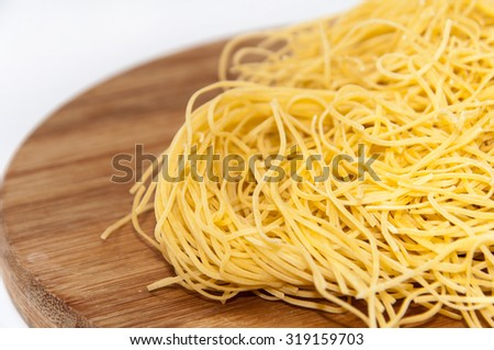 Homemade noodles on a kitchen wooden board.