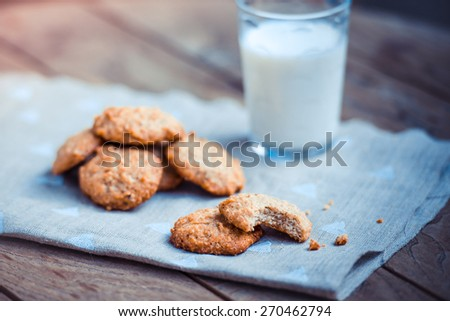 Homemade oat and nut cookies and glass of milk on wooden table - stock photo