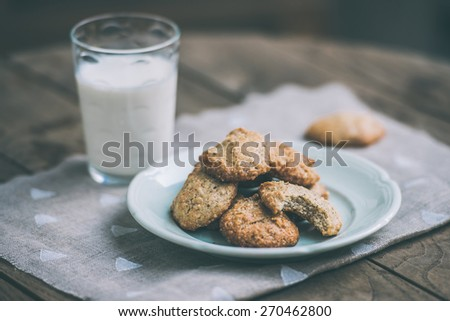 Homemade oat and nut cookies and glass of milk on wooden table. Toned picture - stock photo