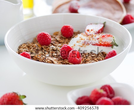 Homemade oat meal granola or muesli with fresh summer fruits â?? raspberry and strawberry with yogurt in a white bowl on a table for breakfast, closeup, selective focus - stock photo