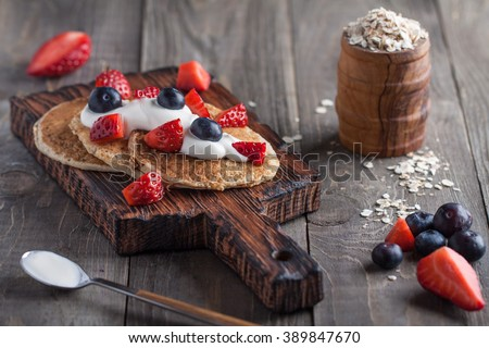 Homemade oat pancakes with vegan yogurt, strawberry and blueberry on the wooden desk - stock photo