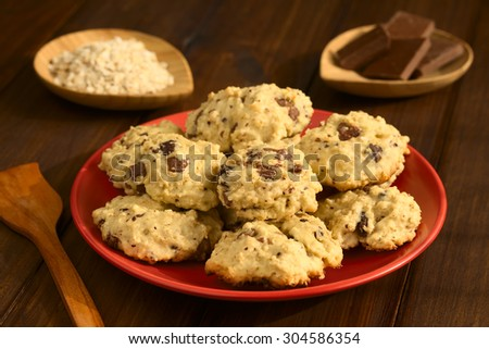 Homemade oatmeal and chocolate cookies on red plate with ingredients in the back, photographed with natural light (Selective Focus, Focus on the front of the cookies on the top) - stock photo
