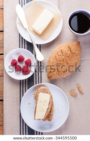 Homemade oatmeal bread on a wooden table with coffee, butter and raspberries for breakfast. Top view