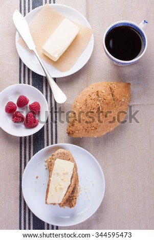 Homemade oatmeal bread on a wooden table with coffee, butter and raspberries for breakfast. Topview