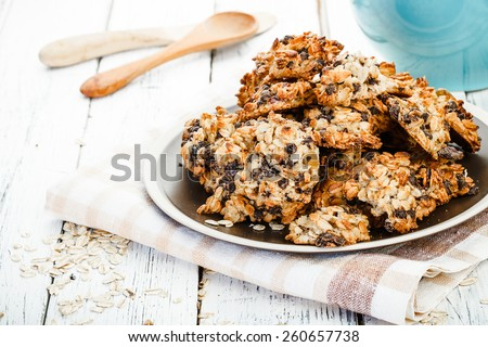 homemade oatmeal cookies and old textile tablecloth on old white wooden table - stock photo