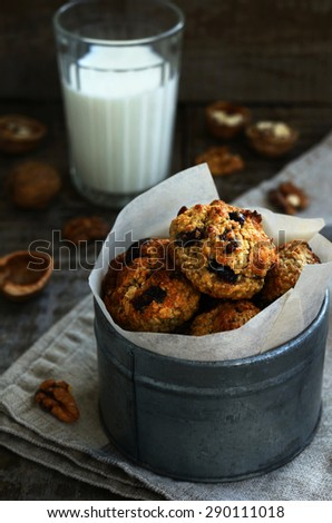 Homemade oatmeal cookies with nuts, raisin and dried cranberries and glass of milk for breakfast. Baked with love. - stock photo