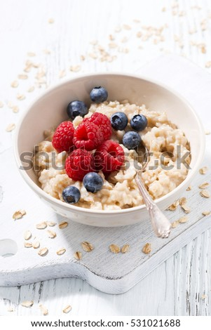 homemade oatmeal with berries on white wooden table, vertical